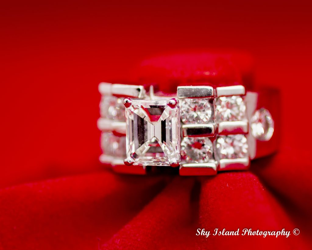 Women's diamond engagement ring on a red setting with five diamonds on each side of center emerald cut diamond. Sky Island photography John Heyward